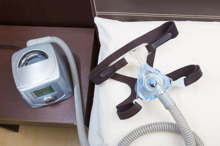 Sleep apnea CPAP headgear mask and hose on white pillow attaching to CPAP machine, for people with sleep apnea or sleep disorder
