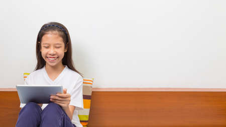 space text: Happy smiling asian girl sitting using computer tablet, room for copy space text Stock Photo