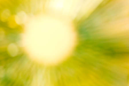 radiate: Blurred abstract background in greenish yellow tone, soft yellow circle with soft straight lines of greenish yellow light radiate outward