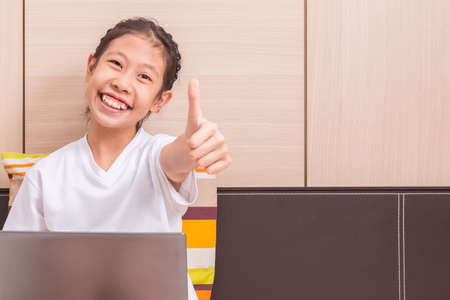 give out: Happy smiling asian girl using notebook computer to study in her bedroom, reaching out her hand to give thumb up to camera, room for copy space text