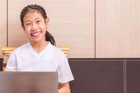 room for copy: Happy smiling asian girl using notebook computer to study on her bed, room for copy space text Stock Photo