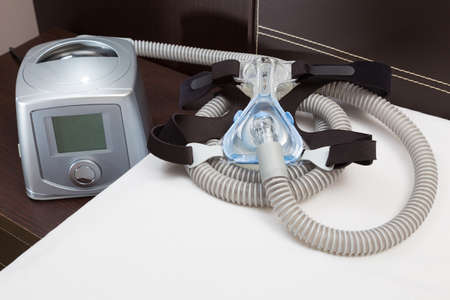 Sleep Apnea CPAP mask, hose, headgear, and machine on bed, selective focus on CPAP mask