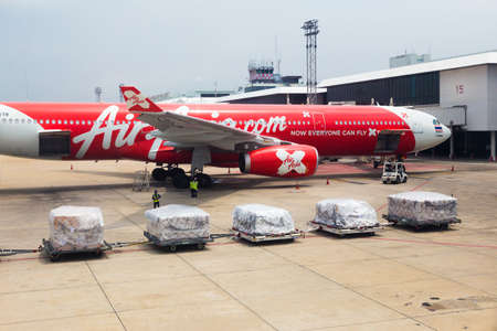 waits: BANGKOK, THAILAND - 24 July 2016 - Air Asia airplane waits for luggage cargos to be loaded at Don Mueng International Airport on July 24, 2016.
