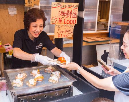 broil: TOKYO, JAPAN - 18 JULY 2016 - Happy smiling woman seller sells seafood dish to her customer at Tsukiji Fish Market in Tokyo, Japan on July 18, 2016. Editorial