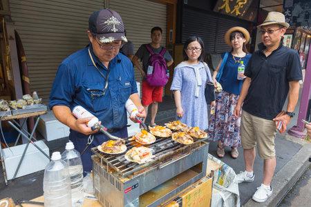fish vendor: TOKYO, JAPAN - 18 JULY 2016 - Jananese man street vendor cooks seafood for his waiting customers at Tsukiji Fish Market in Tokyo, Japan on July 18 2016 Editorial