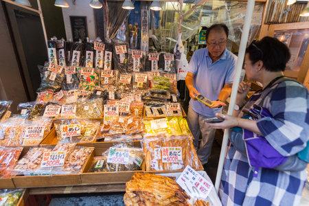 fish vendor: TOKYO, JAPAN - 18 JULY 2016 - Seafood snack vendor shows his customer the price in his shop in Tsukiji Fish Market, Tokyo, Japan on July 18, 2016.