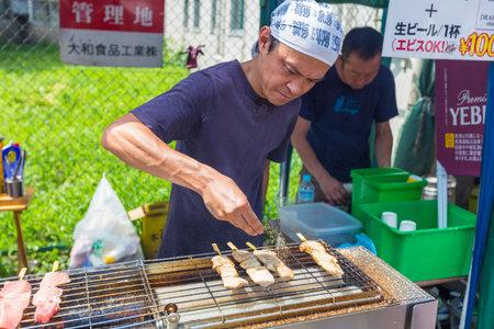 fish vendor: TOKYO, JAPAN - 18 JULY 2016 - Street vendor man cooks fish on sticks at Tsukiji Fish Market in Tokyo, Japan on July 18, 2016