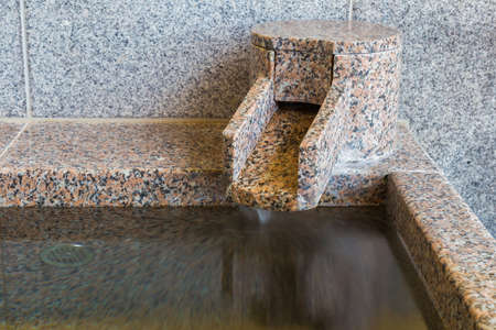 ryokan: Close up section of onsen marble bathtub and marble faucet, Japanese style bath Stock Photo