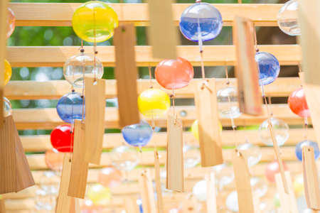 KAWAGOE, JAPAN - 20 JULY 2016 - Colorful glass wind chimes hang from wood structure during Wind Chime Festival at Hikawa Shrine in Kawagoe town, Japan, on July 20, 2016.  Selective focus on second row of the wind chimes