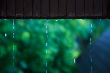 trickle down: Rain water dropping from old rusted metal roof on a cold day, slow shutter speed to show water movement