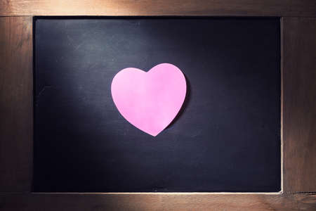 hearted: Empty pink hearted shape sticky note on blackboard with concentrated light beam for dramatic feel, vintage retro look Stock Photo