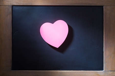 light hearted: Empty pink hearted shape sticky note on blackboard with concentrated light beam for dramatic feel, vintage retro look Stock Photo
