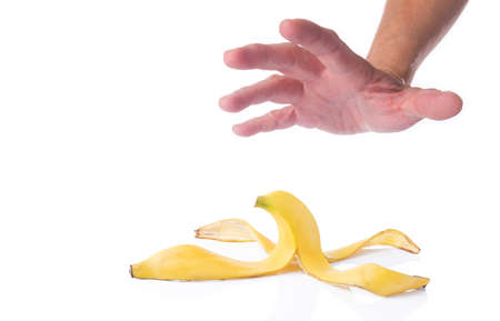 room for copy: Mans hand reaching for a peeled banana skin, isolated white background with room for copy space