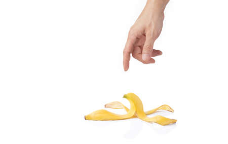 Mans hand reaching for a peeled banana skin, isolated white background with room for copy space