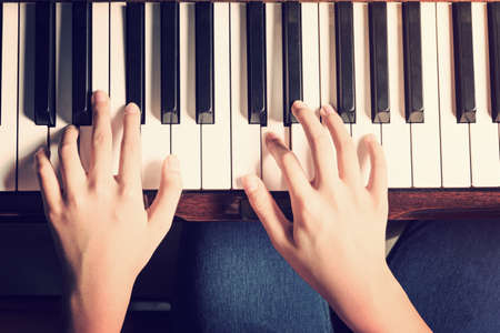 Female hands playing piano with high contrast vintage and retro look added