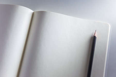 side lighting: Opened blank white notebook and pencil on white background with side lighting