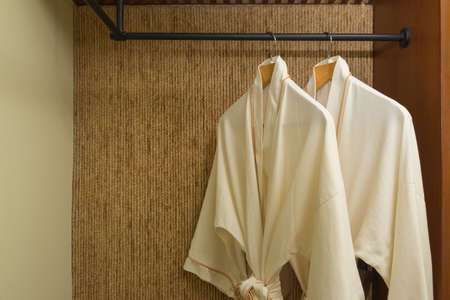 warmly: two off white color bathrobes hanging in warmly design closet, room for copy space