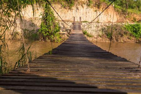 brige: Old wooden sling brige hanging suspended above river in northern Thailand