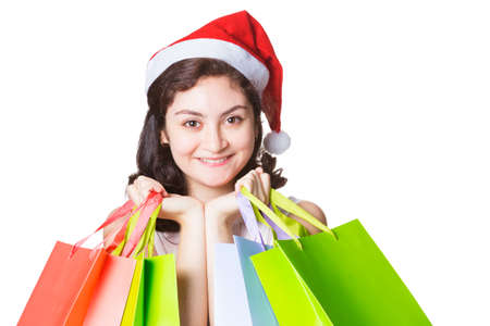 chirstmas: Happy smiling beautiful woman wearing chirstmas hat holding colorful shopping bags on isolated white background Stock Photo
