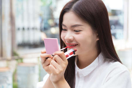 young attractive asian woman putting on makeup, red lipstick