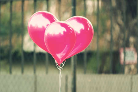redish pink balloons grouping into heart shape, outdoor in vintage color tone Stock Photo