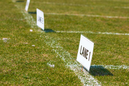 Lane signs on grass field for elementary school track and field tournament Stock Photo