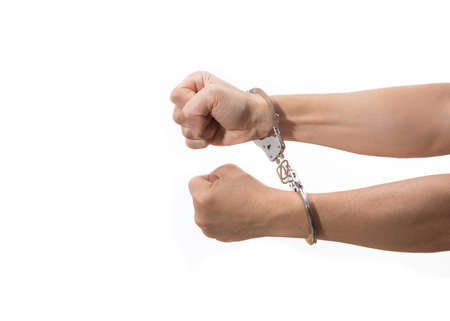 trapped: two hands with tight fists on handcuff reaching out on white background, room for copyspace