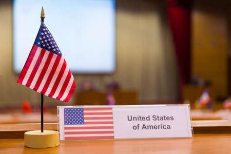 United of America's kleine Flagge auf Besprechungstisch, mit verschwommenen Tagungsraum Hintergrund Standard-Bild