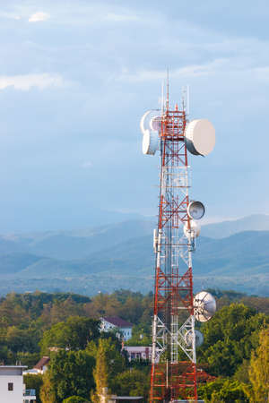 telecommunication tower against cloudy blue sky and distant mountains, with room for copy space