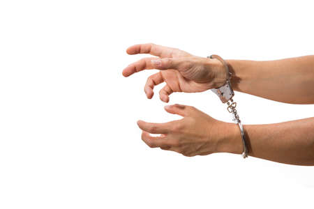 handcuffs: male hands on handcuffs, with white isolated background Stock Photo