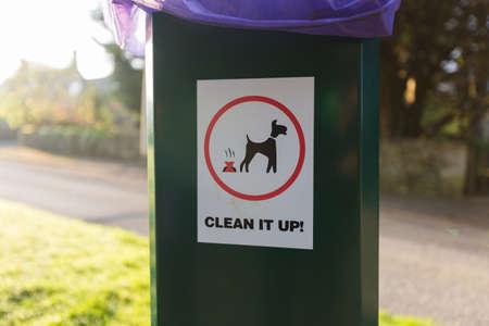 Panneau d'avertissement pour nettoyer l'affichage des déchets de votre animal sur le côté d'un conteneur à déchets en plastique vert Banque d'images - 76530860