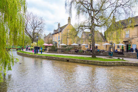 Bourton On The Water, England - 7 April 2017 - People enjoy their day along the water on a fine day at Bourton On The Water, England on April 7th, 2017.