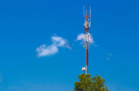 skinny tall telecommunication tower against deep blue sky and white fluffy clouds with foreground tree