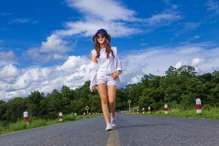 young attractive happy asian teenager woman, in white shirt, short, sunglasses and hat, walking casually and confidently on a road surrounded by nature, concept of carefree and happy free time