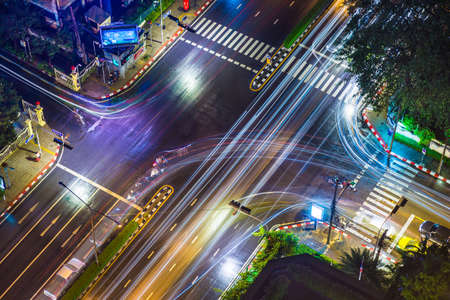 paso de peatones: Bangkok, Thailand - 6 July 2017 - View of a street intersection in Bangkok on a rainy night shows cars and motorbike going about their business, on July 6, 2017 in Bangkok, Thailand