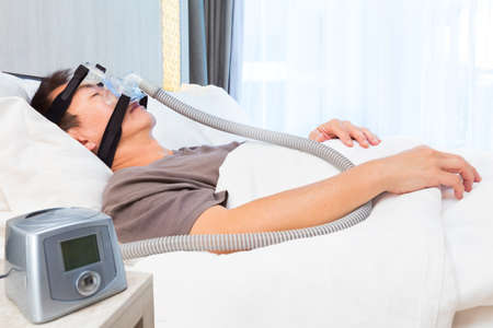 middle age asian man sleeping in his bed wearing CPAP mask connecting to air hose and CPAP machine, device for people with sleep apnea Stock Photo