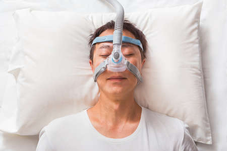 middle age asian man sleeping in his bed wearing CPAP headgear mask connected to air hose, device for people with sleep apnea