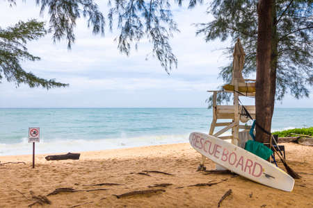 sandy beach of Phuket, Thailand with empty coast guard station with rescue surfboard and swimming prohibited sign