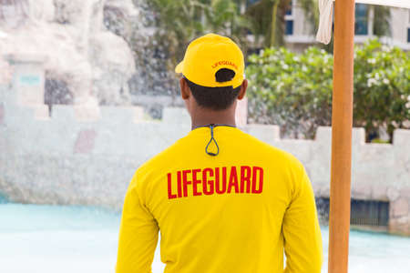on duty: Back side of lifeguard man wearing yellow lifeguard shirt and cap, standing on duty