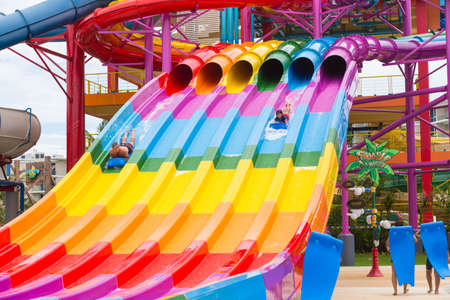 Phuket, Thailand - 8 July 2017 - Happy vacationers slide down giant sliders at Splash Jungle Water Theme park in Phuket, Thailand on July 8, 2017