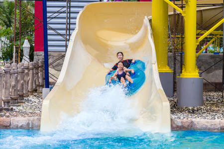 Asian teenagers enjoying their water slider ride at a water theme park in Phuket, Thailand