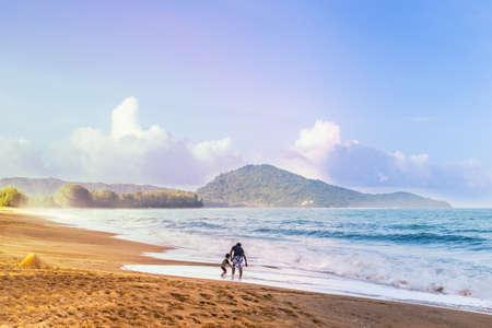 Asiatische Familie, Vati und Sohn, ihre Zeit an einem Strand in Phuket, in Thailand, mit Ansicht von schönem Meer und von Himmel im Hintergrund genießend, gut für positives Gefühlthema