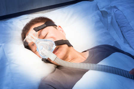 middle age asian man sleeping in his bed wearing CPAP mask connecting to air hose, device for people with sleep apnea, night time blue color effect