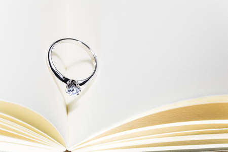 beautiful diamond ring on blank open book with heart shape shadow, room for copy space, good concept for wedding, engagement, or special occasions