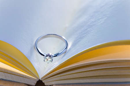beautiful diamond ring on blank open book with cool and warm color tone, room for copy space, good concept for wedding, engagement, or special occasions Stock Photo