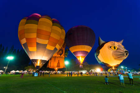 Chiang Mai, Thailand - 04 March 2016 - Hot air balloons light up on the field against blue evening sky with people walking around at Chiang Mai Balloon Festival on March 04, 2016 in Chiang Mai, Thailand.