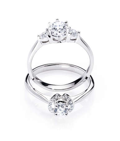 two diamond engagement wedding rings on isolated white background with light reflection, one ring standing up, one ring laying down