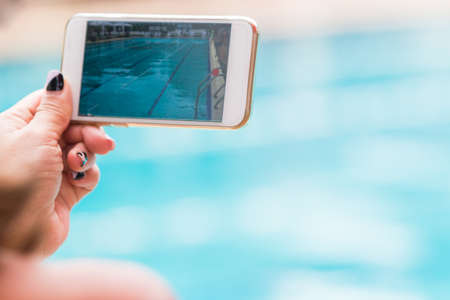 woman hand holding her phone recording swimming pool activities, selective focus, and room for text or copy space Stock Photo