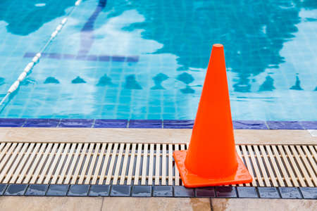 wet bright orange cone placed by the swimming pool side as safety precaution sign, good for safety concept 版權商用圖片 - 87819139