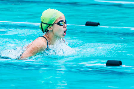 Chiang Mai, Thailand - 11 October 2017 - young female swimmer races in breath stroke and raises up to catch her breath at a school swimming pool in Chiang Mai, Thailand on October 11, 2017 Redakční
